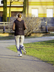 young woman with headphones jogging in park