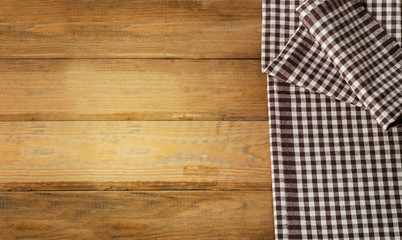 Brown checkered Tablecloth textile on  wooden background