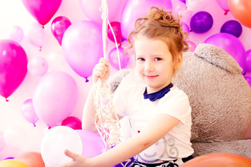 Portrait of smiling girl on balloons background