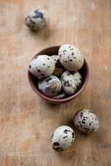 Quail eggs in a ceramic bowl, high angle view, selective focus