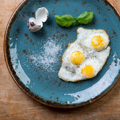 Above view of fried quail eggs on a turquoise plate, close-up