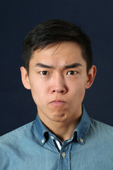 Displeased young Asian man looking at camera