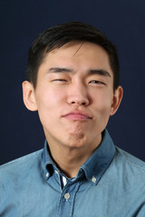 Pleased young Asian man making face and looking at camera