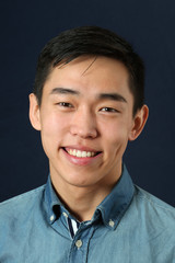 Smiling young Asian man looking at camera