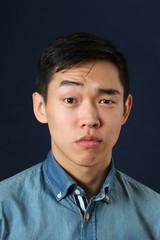 Serious young Asian man looking at camera