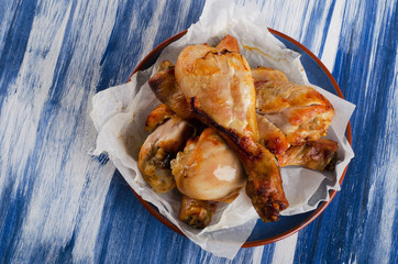 Roasted chicken legs on  blue plate.