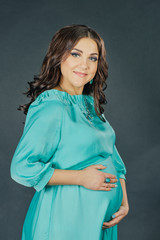 pregnant woman in a turquoise dress on a dark background