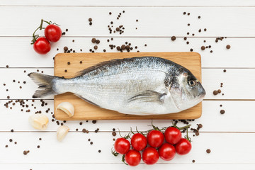 Fresh dorado fish on wooden cutting board with cherry tomatoes