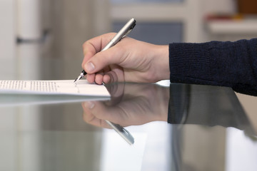Hand of man signing formal paper