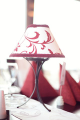 White lamp with red patterns on a table
