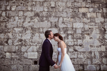 Bride and groom kissing near brick wall
