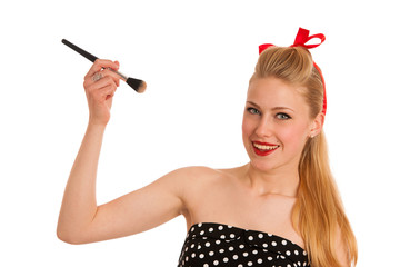 Retro style pin up girl with blonde hair applying makeup