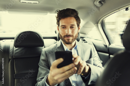 Hipster man in car. Typing text message on mobile phone