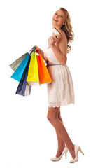 Beautiful young blonde caucasian woman holding vibrant shopping