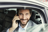 Fototapety Cheerful business man on mobile phone in rear of the car
