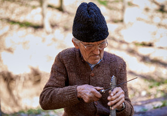 old man sharpening a chainsaw