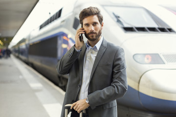 Man on the cell phone. Platform station. Train on background