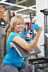 Happy woman tries dumbbell in sport shop