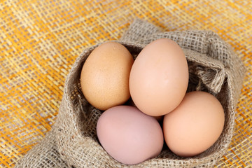 Chicken brown eggs in sack bag over bamboo weave background.