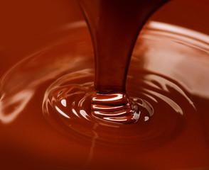 Chocolate flow. Close up of liquid hot chocolate pouring closeup
