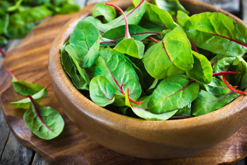 Fresh chard leaves in wooden bowl