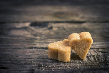 two brown cane sugar  hearts on old wooden table