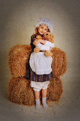 girl hugging a bear near the hay.