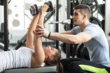 Fitness instructor  exercising with his client at the gym poster