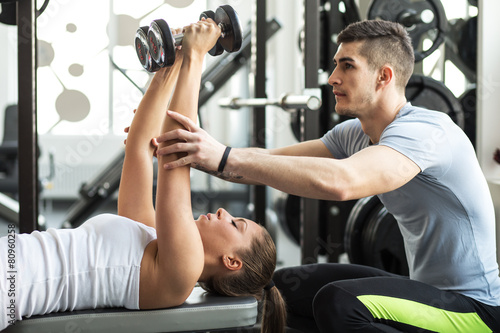Zdjęcia na płótnie, fototapety, obrazy : Fitness instructor  exercising with his client at the gym