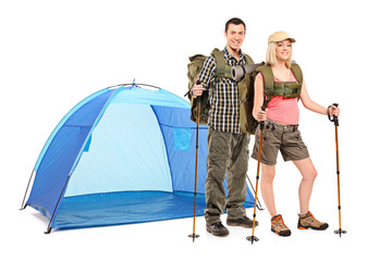Male and female hiker standing next to a blue tent