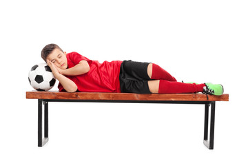 Kid in a football uniform sleeping on a bench