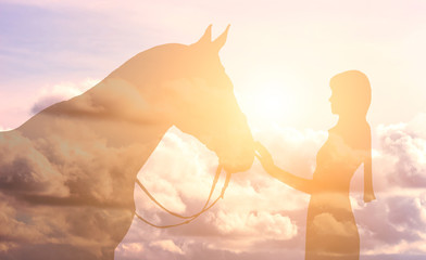 Silhouette of a girl and a horse on a background of the sky