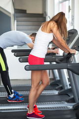 Young man and woman at the gym after running on treadmill