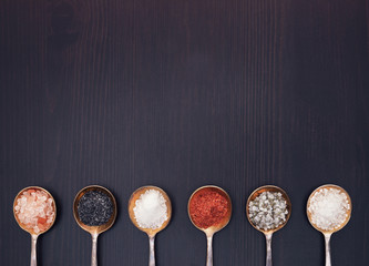 Salt in vintage metal spoons on a wooden background