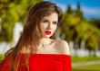 Outdoor portrait of fashion brunette model in red dress. Romanti