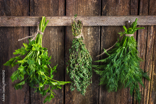 Papiers peints Herbe, epice Bunch of thyme, dill and parsley hanging on old wooden board