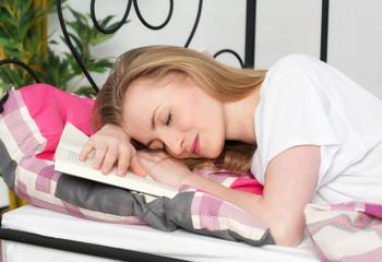 Junge Frau ist beim Lesen im Bett eingeschlafen
