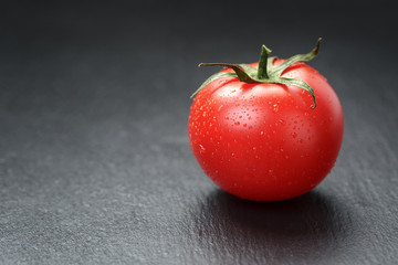 ripe washed tomato on slate background