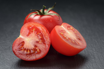 ripe washed tomatoes on slate background