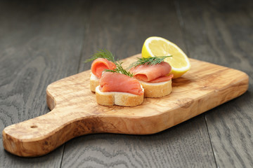 baguette slices with curred salmon and dill on wood table