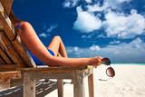 Fototapety Woman at beach holding sunglasses