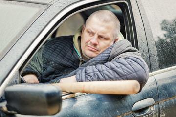 Aggressive man with a baseball bat in car at outdoors