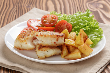 fried fish fillet with vegetables on wood table