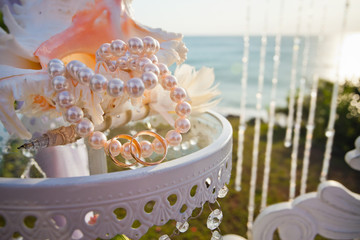 Wedding rings at table with beautiful shell