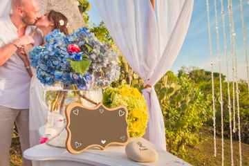 Wedding frame and honeymooners at background