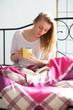 Blonde junge Frau mit Kaffee und Buch im Bett