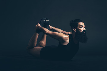 Bearded Guy Doing Dhanurasana Pose Facing Right