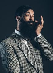 Gentleman with a beard tweaking his mustache