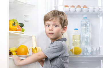 Little cute boy holding banana near open fridge