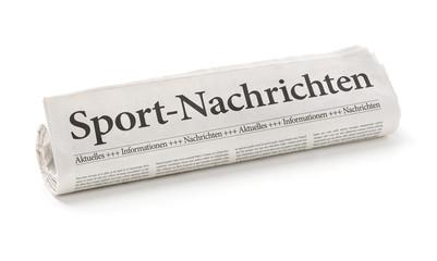 Zeitungsrolle mit der Überschrift Sport-Nachrichten